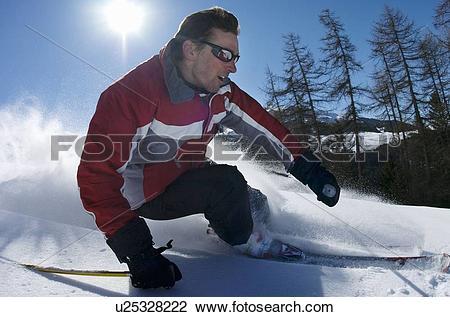 Stock Photo of Skier carving through powder snow u25328222.