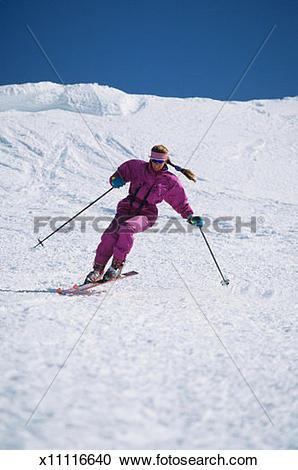 Stock Photography of Female skier carving ski slope, Kirkwood Ski.