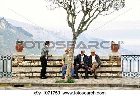 Stock Photograph of Sicily, Italy Men chatting in the square of.