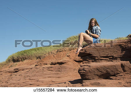 Stock Photo of Girl sitting on rock, Cavendish Beach, Green Gables.
