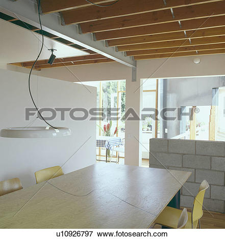 Picture of Pendant light above pale wood table in modern openplan.