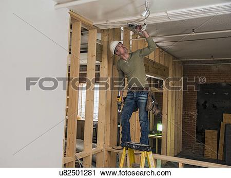 Stock Photography of Construction worker drilling in ceiling.