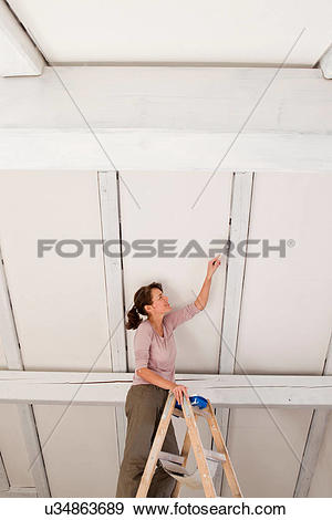 Stock Photograph of Woman on stepladders painting white ceiling.