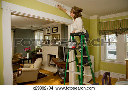 Stock Photo of Mature woman standing on step ladder, painting.