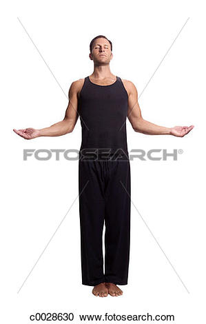Stock Photography of A man practices yoga, centering himself in a.