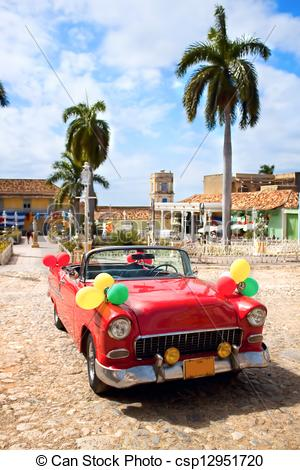Stock Photo of Red oldtimer car in the central square of Trinidad.