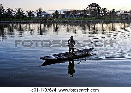 Stock Photo of Fisherman on boat at sunset, Da Nang, Central.