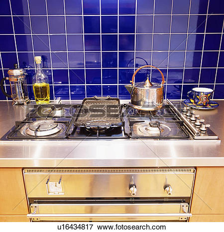 Picture of Blue ceramic wall tiles above stainless steel gas hob.