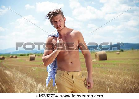 Stock Photo of topless man outdoor on a cereal field with a straw.