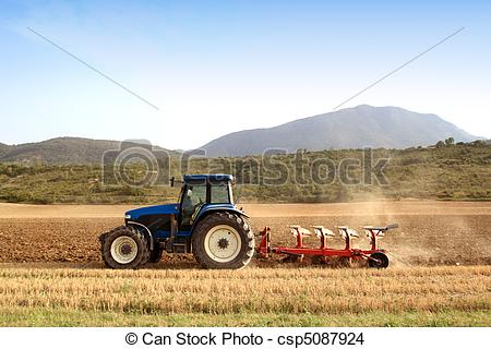 Stock Photo of Agriculture plowing tractor on wheat cereal fields.