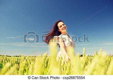 Stock Images of smiling young woman on cereal field.
