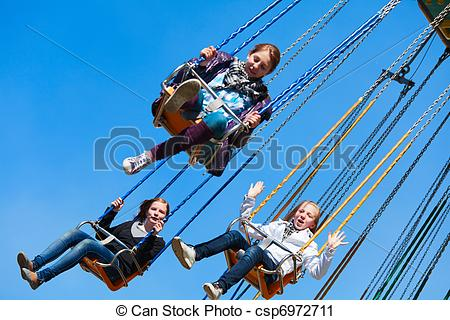 Stock Photography of Teenage girls on the chain swing carousel.