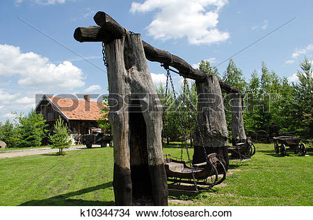 Stock Photo of Retro swing carriage hang on chains on tree trunk.