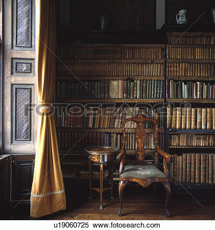 Stock Image of Inlaid antique chair in front of bookshelves with.