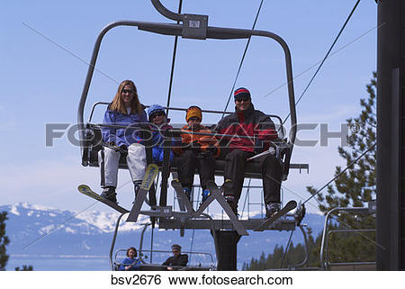 Stock Images of A family riding a chairlift while skiing at.