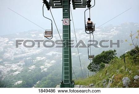 Stock Images of Capri, Italy; Woman riding chairlift to the top of.