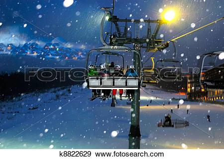 Stock Photograph of people ride in the chairlift at night k8822629.