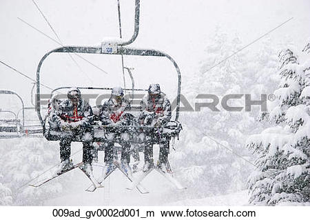 Stock Photo of Three male skiers ride a chairlift in the snow at.