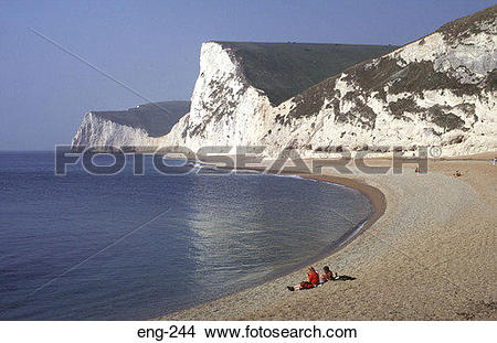 Stock Photo of People Sitting under Chalk Cliffs Dorset England.