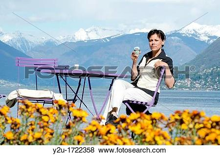 Pictures of Woman sitting down in a patio and drinking a glass of.