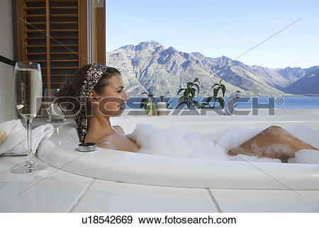 Stock Photograph of Woman taking a bubble bath with champagne with.