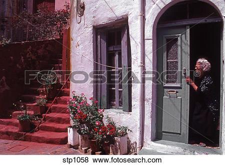 Pictures of Old cretan woman standing in the doorway of her.