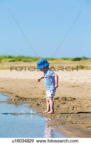 Stock Photograph of Small boy on beach throwing sand into sea.