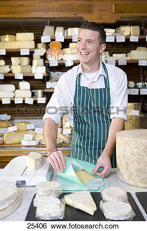 Stock Images of Salesman standing at counter wrapping wedge of.