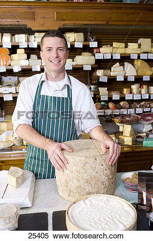 Stock Image of Salesman standing at counter with cheese in cheese.