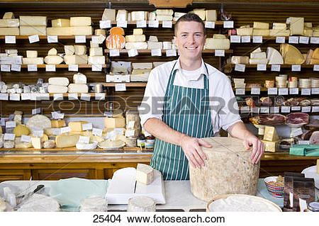 Stock Photo of Salesman standing at counter with cheese in cheese.