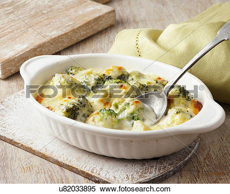 Stock Image of Broccoli baked in cheese sauce on wooden board.