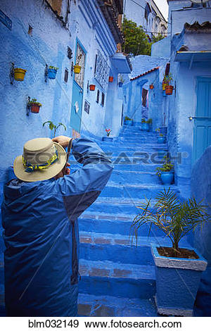 Stock Photograph of Man photographing blue historical village.