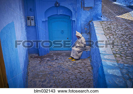 Stock Photo of Caucasian hooded man sitting on colorful historical.