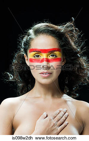 Stock Photo of Woman with red and yellow face paint, hand on chest.