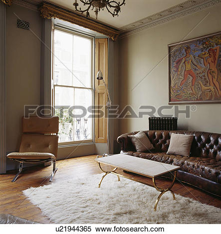 Stock Image of Brown leather Chesterfield sofa and metal framed.