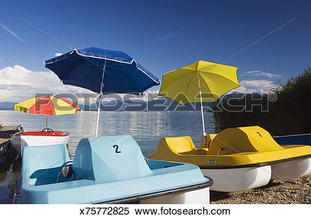 Stock Image of funny boats, Pedalo with sunshade at Lake Chiemsee.