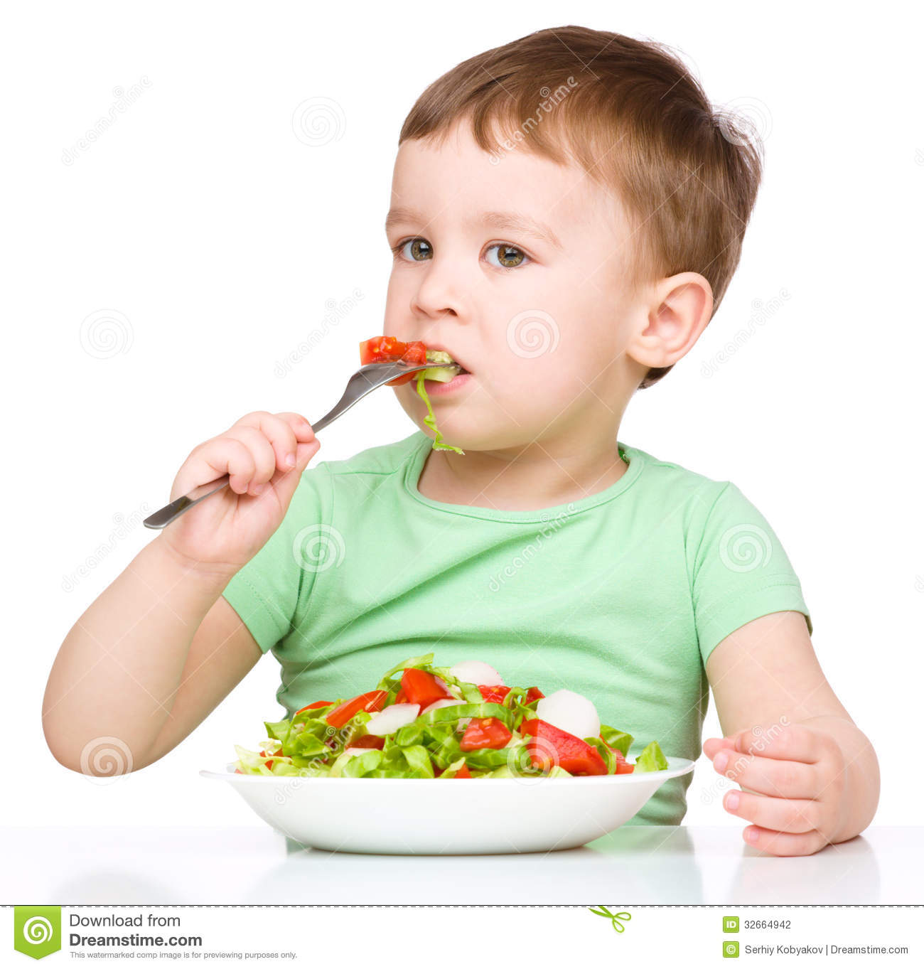 Cute Little Boy Is Eating Vegetable Salad Stock Photo.