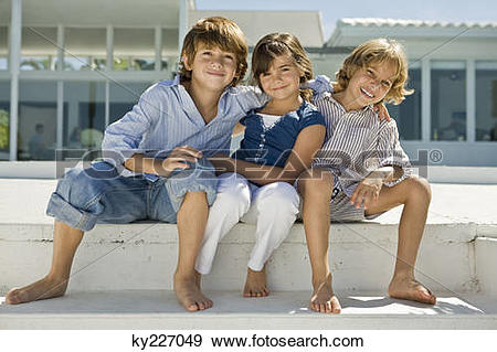 Stock Photograph of Portrait of three children sitting together.
