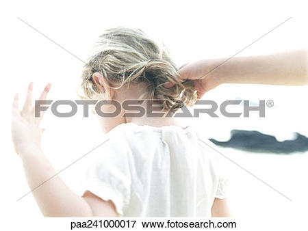 Picture of Hand touching child's hair, rear view, blurred.