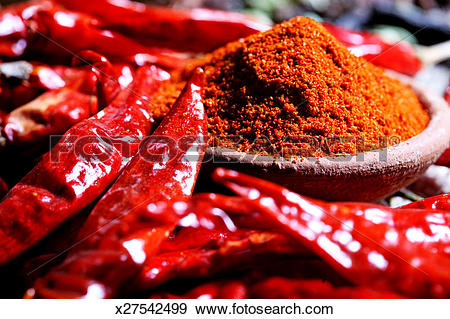Stock Photograph of Close up of chili powder and red chilies.