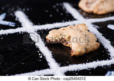 Stock Photography of Chocolate chip cookies on noughts and crosses.