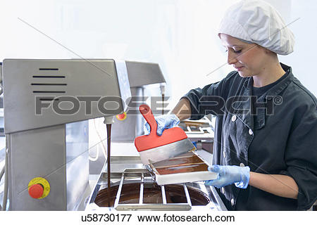 Picture of Chocolatier smoothing chocolate in moulds u58730177.