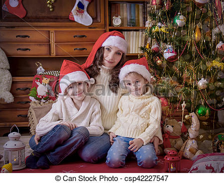 Stock Photo of Children sitting with mother under Christmas tree.