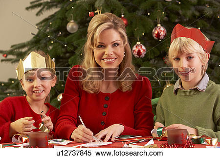 Stock Image of Mother And Children Making Christmas Cards Together.