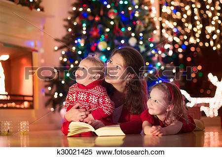 Stock Image of Mother and children at home on Christmas eve.
