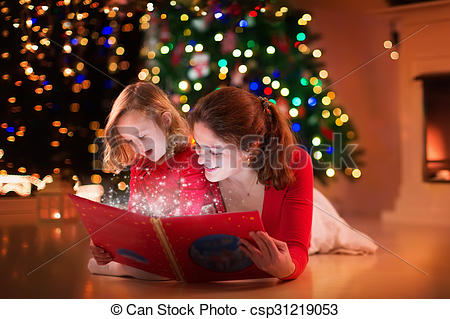 Stock Images of Mother and daughter reading at fire place on.