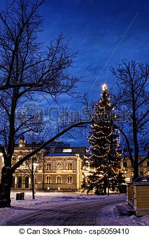 Stock Photography of Illuminated tall Christmas tree in snowy old.