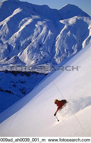 Stock Photo of Extreme skier skis down steep snow covered mountain.