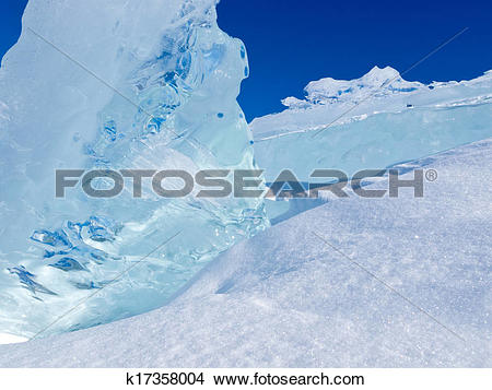 Stock Photo of Clear glacier ice chunks with snow and blue sky.