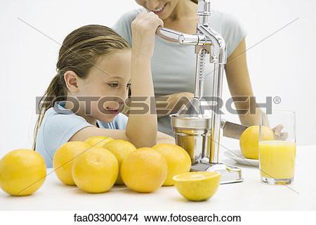 Stock Photo of Girl making fresh orange juice with citrus press.